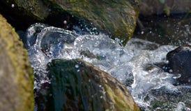 Spruzzando acqua che scorre sulle rocce Fotografie Stock Libere da Diritti
