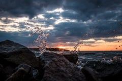 Spruzzando acqua sui precedenti di tramonto Immagini Stock Libere da Diritti