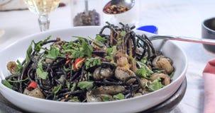 Spruzzando i fiocchi freddi sopra pasta con i calamari seppia ed inchiostro Immagini Stock