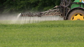 Spruzzando pota il campo con il trattore e lo spruzzatore, coltivanti, raccolto stock footage
