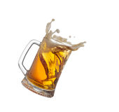 Spruzzando tazza con la birra isiolated sul bianco fotografia stock libera da diritti