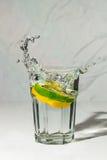 Spruzzata del latte di calce e del limone in vetro Fotografie Stock