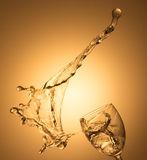 Spruzzata del vino bianco sul fondo dell'oro Fotografia Stock