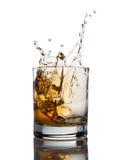 Spruzzata del whiskey isolata su un bianco Immagine Stock
