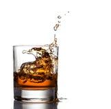 Spruzzata del whiskey isolata su un fondo bianco Fotografie Stock