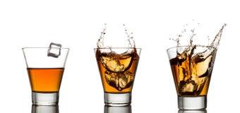 Spruzzata del whiskey in vetro isolato su un bianco Fotografia Stock Libera da Diritti
