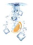 Spruzzata dell'acqua con i cubi e l'arancio di ghiaccio fotografia stock libera da diritti
