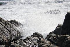 Spruzzata dell'acqua dell'oceano la roccia Fotografia Stock