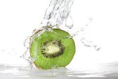 Spruzzata dell'acqua in frutta di kiwi Fotografia Stock