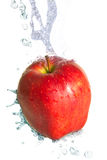 Spruzzata dell'acqua su una mela rossa fresca Fotografie Stock Libere da Diritti