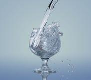 Spruzzata dell'acqua in un vetro Fotografie Stock Libere da Diritti