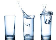 Spruzzata dell'acqua in vetri su bianco Fotografie Stock