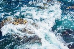 Spruzzata dell'onda del mare dell'oceano sulla riva rocciosa, lotto di schiuma ed acqua blu scuro Fotografia Stock