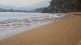 Spruzzata dell'onda del mare sulla spiaggia sabbiosa nel giorno di autunno video d archivio