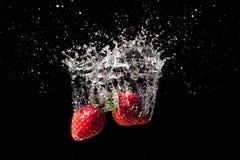 Spruzzata della frutta della fragola grande in acqua fotografie stock