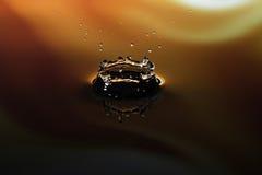 Spruzzata della goccia di acqua su fondo giallo arancione Immagini Stock