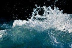 Spruzzata di acqua tempestosa nell'oceano su un fondo nero Fotografia Stock Libera da Diritti