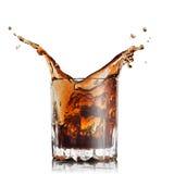 Spruzzata di cola in vetro con i cubi di ghiaccio Fotografia Stock