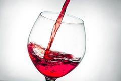 Spruzzata di versamento del vino rosso in vetro fotografie stock libere da diritti