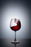 Spruzzata di vino rosso in un vetro Fotografia Stock