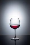 Spruzzata di vino rosso in un vetro Fotografie Stock Libere da Diritti