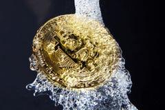 Spruzzata dorata dell'acqua e del bitcoin Lavare e di soldi Fotografia Stock