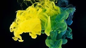 Spruzzata gialla e ciano dell'inchiostro su fondo nero video d archivio