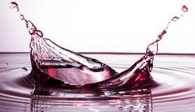 Spruzzata liquida rossa dell'acqua con le gocce Fotografia Stock