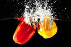 Spruzzata rossa e gialla dell'acqua del pepe Fotografia Stock Libera da Diritti