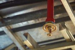 Spruzzatore automatico del fuoco del soffitto nel sistema rosso della tubatura dell'acqua immagini stock