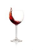 Spruzzatura del vino rosso in un vetro Fotografia Stock