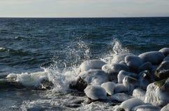 Spruzzatura dell'acqua alle rocce ghiacciate Immagine Stock