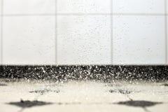 Spruzzatura delle gocce che colpiscono il bathroomfloor Fotografie Stock
