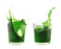 Spruzzi dal cubetto di ghiaccio nei vetri dell'acqua verde o beva Immagini Stock Libere da Diritti