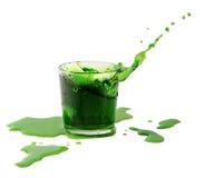 Spruzzi dal cubetto di ghiaccio in un vetro dell'acqua verde o beva Fotografia Stock