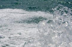 Spruzzi e spumi contro una superficie ondulata del mare immagini stock libere da diritti