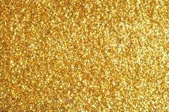 Spruzzi il fondo della polvere di oro di scintillio Immagini Stock