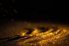 Spruzzi la polvere di oro su un fondo nero Immagine Stock