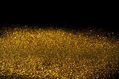 Spruzzi la polvere di oro su un fondo nero Immagine Stock Libera da Diritti