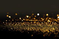 Spruzzi la polvere di oro su un fondo nero Fotografie Stock