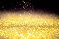 Spruzzi la polvere di oro sul nero Fotografia Stock