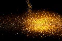 Spruzzi la polvere di scintillio dell'oro su un fondo nero Immagini Stock