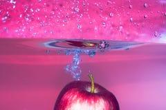 Spruzzi-serie: mela rossa con priorità bassa rossa fotografie stock