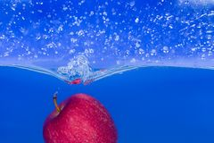 Spruzzi-serie: mela rossa con priorità bassa blu Fotografie Stock Libere da Diritti