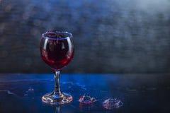 Spruzzi in succo o vino rosso in un bicchiere di vino Immagine Stock