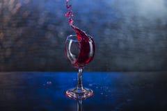 Spruzzi in succo o vino rosso in un bicchiere di vino Fotografie Stock Libere da Diritti