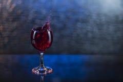 Spruzzi in succo o vino rosso in un bicchiere di vino Immagini Stock