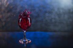 Spruzzi in succo o vino rosso in un bicchiere di vino Immagini Stock Libere da Diritti