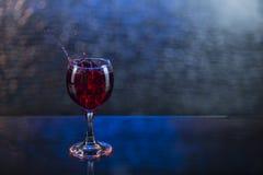 Spruzzi in succo o vino rosso in un bicchiere di vino Fotografia Stock Libera da Diritti