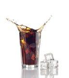 Spruzzi in vetro di cola con i cubi di ghiaccio Immagine Stock Libera da Diritti